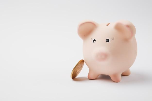 Bliska różowy piggy bank pieniędzy, złote monety na białym tle na tle białej ściany. akumulacja pieniędzy, inwestycje, usługi bankowe lub biznesowe, koncepcja bogactwa. skopiuj makiety reklamowe.
