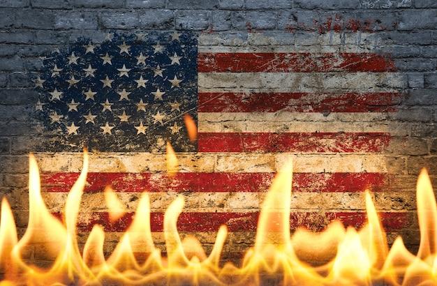 Bliska ściana z pomalowaną amerykańską flagą usa w płomieniach jako symbol świata w ogniu, niebezpieczeństwa, kryzysu politycznego, gospodarczego lub pandemii