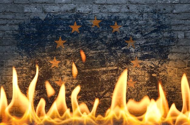 Bliska ściana z pomalowaną flagą ue unii europejskiej w płomieniach jako symbol świata w ogniu, niebezpieczeństwa, kryzysu politycznego, gospodarczego lub pandemii