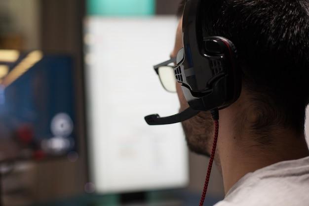 Bliska skoncentrowany mężczyzna grający w profesjonalne strzelanki. transmisje e-sportowe.