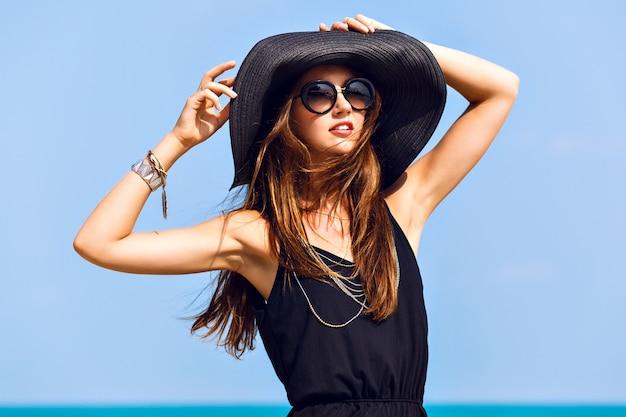 Bliska słoneczny letni portret pięknej kobiety z puszystymi brunetkami długimi włosami, uśmiechnięta, bawiąca się w pobliżu błękitnego oceanu, nosząca okulary przeciwsłoneczne, strój i kapelusz, styl wakacyjny, jasne kolory