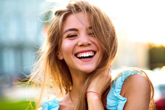 Bliska słoneczny portret pięknej, wspaniałej kobiety z naturalnym makijażem i dużym niesamowitym uśmiechem patrząc na kamery, jasne światło słoneczne, pozytywny nastrój.