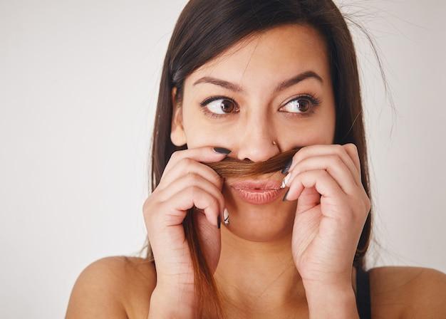 Bliska śmieszna młoda kobieta wkładając włosy między nos a wargę i odwracając wzrok.