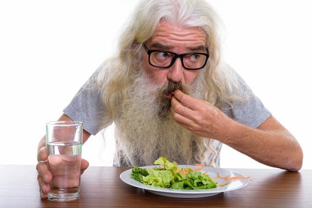 Bliska starszy brodaty mężczyzna myśli i noszenie okularów
