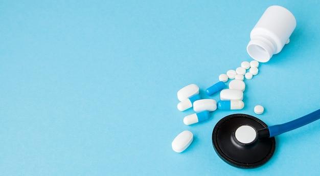 Bliska stetoskop i pigułki wysypują się z butelki pigułki na niebieskim tle. koncepcja medycyny, ubezpieczenia medycznego lub apteki.