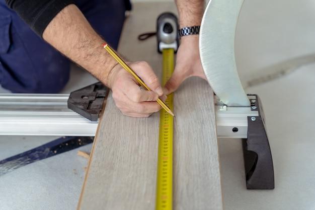 Bliska stolarza pomiaru laminatu drewnianego, aby położyć drewnianą podłogę tarasową