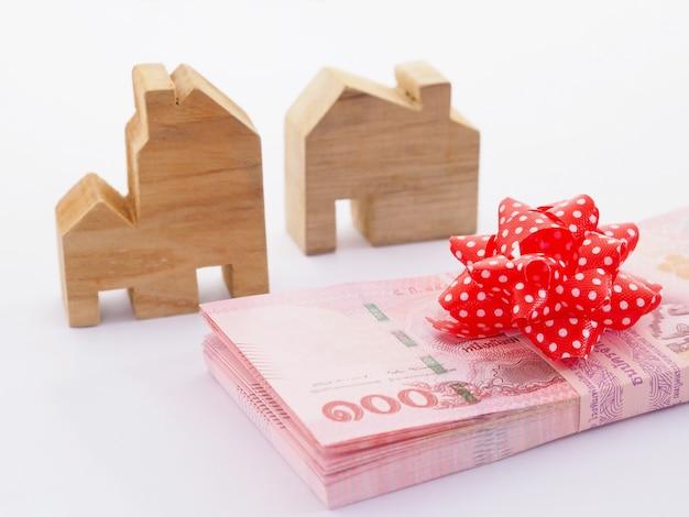 Bliska stos banknotów z czerwoną kokardą i drewniany model domu na białym tle