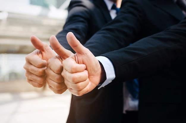 Bliska strony grupy przystojny zespół ludzi biznesu w kolorze pokazując kciuk do góry