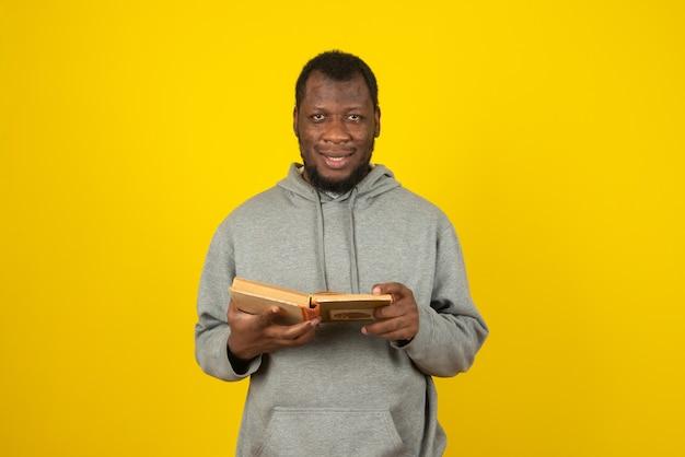 Bliska strzał african-american uśmiechnięty mężczyzna, czytając książkę w ręku, stoi nad żółtą ścianą.