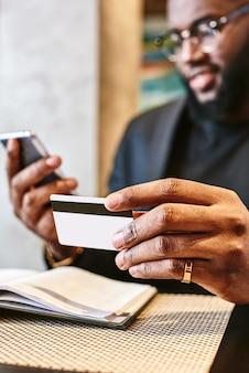 Bliska strzał african mans ręce trzymając telefon komórkowy i kartę kredytową