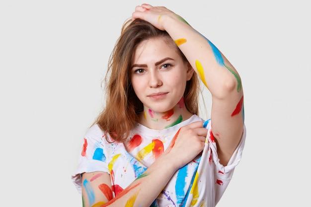 Bliska strzał atrakcyjnej młodej artystki, poplamił ubrania farbami po wykonaniu kolorowych szkiców, ma poważne spojrzenie na kamerę