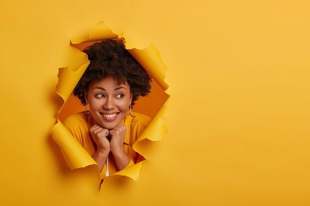 Bliska strzał całkiem wesoła kobieta trzyma obie ręce pod brodą, wyraża przyjazną, radosną postawę, wstaje optymistycznie, nosi żółte ubranie, odwraca wzrok, pozuje na rozdartym tle