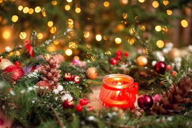 Bliska strzał czerwonej płonącej świecy w bożonarodzeniowy wieniec z jasnym kolorowym tłem