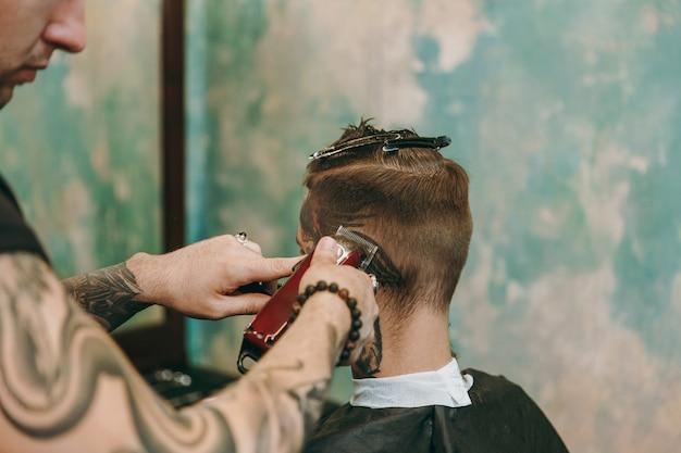 Bliska strzał człowieka coraz modne strzyżenie w fryzjera. męski fryzjer w tatuażach obsługujący klienta.