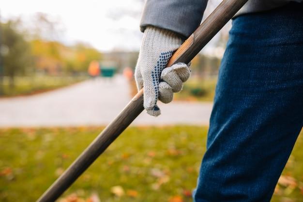 Bliska strzał człowieka z grabią w rękach grabienie liści w jesiennym parku.