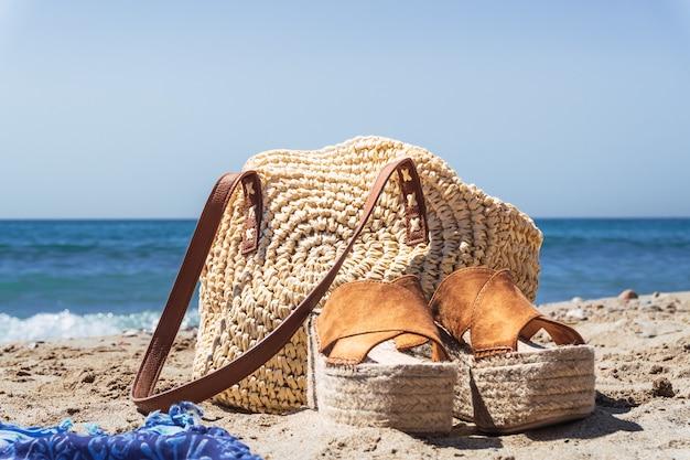 Bliska strzał damskiej torebki i butów na plaży