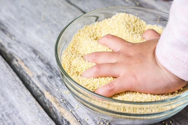 Bliska strzał dłoni dziecka umieścić w misce świeżego całego ziarna amarath