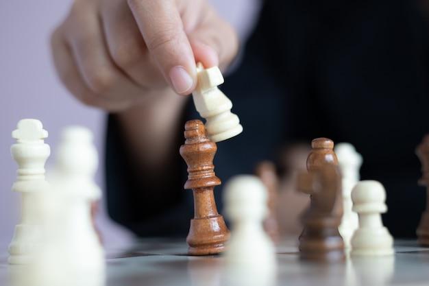 Bliska strzał dłoni kobiety biznesu grającej na szachownicy, aby wygrać, zabijając króla przeciwnika metafora zwycięzca konkursu biznesowego i przegrany wybierz ostrość płytka głębia ostrości