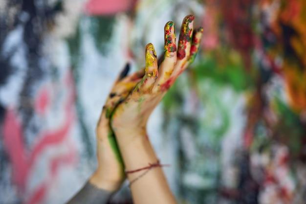 Bliska strzał dłoni w kolorowych farbach kobiecej malarki z abstrakcyjnym malarstwem w