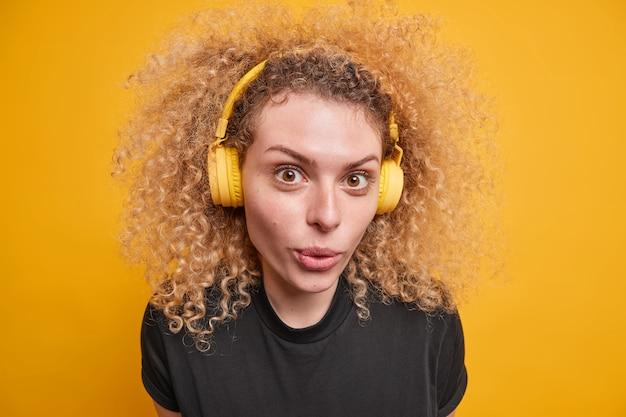 Bliska strzał dobrze wyglądającej kręcone nastolatka nosi słuchawki bezprzewodowe na uszach cieszy się jakością dźwięku słucha muzyki trzyma usta złożone ubrana w dorywczo czarny t shirt na białym tle nad żółtą ścianą