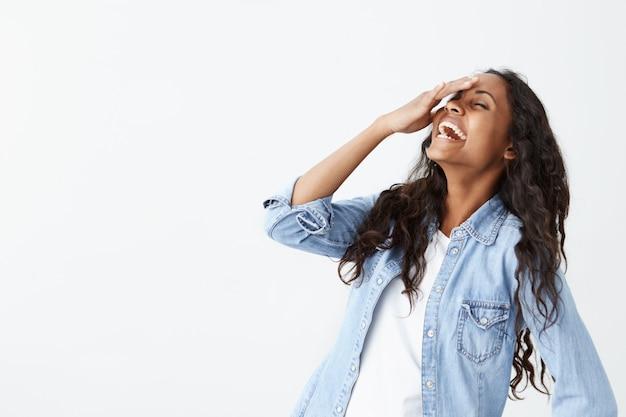 Bliska strzał dobrze wyglądającej wesołej pozytywnie młodej afroamerykańskiej kobiety w dżinsowej koszuli z czarnymi długimi włosami, uśmiechając się szeroko, szczerze się śmiejąc, pokazując swoje białe zęby podczas zabawy