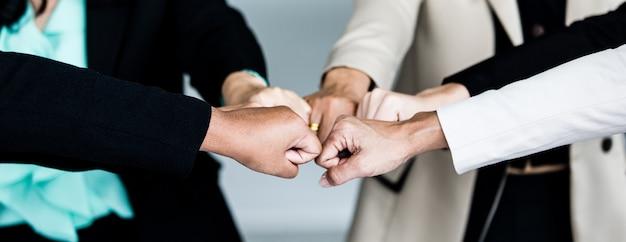 Bliska strzał dotykania pięściami niezidentyfikowanych niezidentyfikowanych udanych koleżanek kobieta interesu grupy stojąc razem w formalnym garniturze zachęcają do wzmocnienia zaufania jedności zobowiązania.