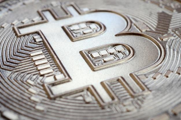 Bliska strzał fizycznego bitcoin z błyszczącą powierzchnią reliefu z czekolady. abstrakcyjny obraz waluty kryptograficznej w formie jadalnej