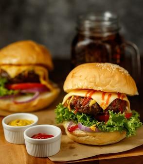 Bliska strzał gotowych do spożycia domowych hamburgerów wołowych ze świeżymi warzywami z dwóch kolorów nadrabiania zaległości.