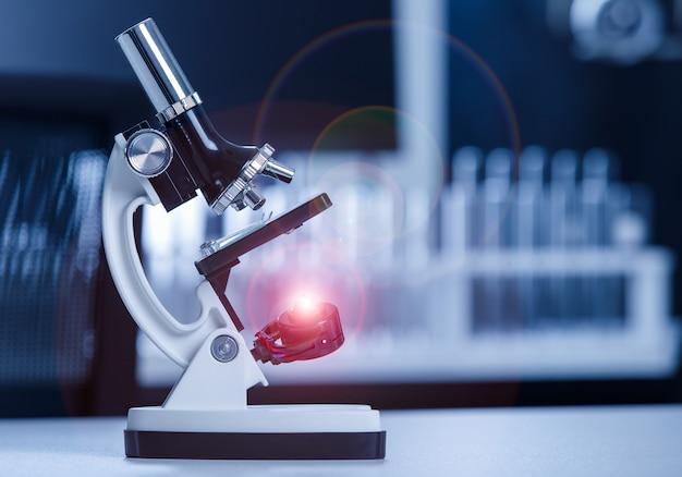 Bliska strzał instrumentu mikroskopu naukowego z świecącym światłem flary na próbce soczewki i szklanej płytki w laboratoryjnym biurku do monitorowania koronawirusa covid 19.