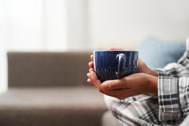 Bliska strzał kobiecej dłoni trzymającej kawę. koncepcja relaksu w domu.