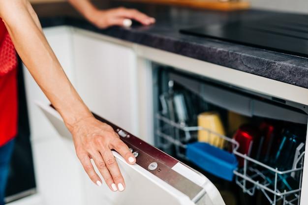 Bliska strzał kobiecej dłoni wyjmując czyste naczynia ze zmywarki.