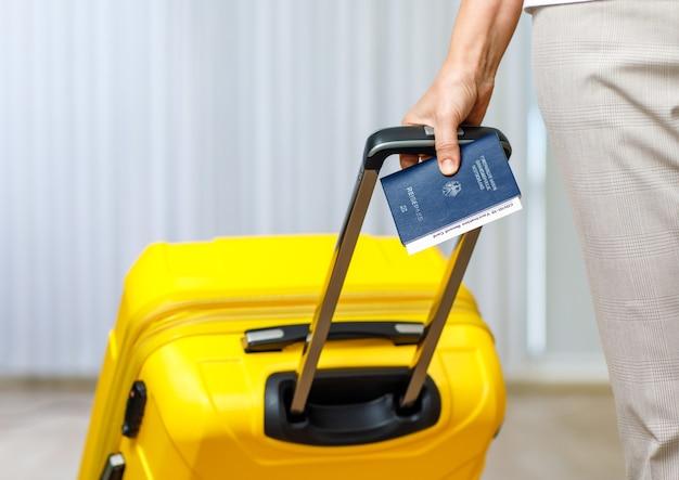 Bliska strzał kobiecej ręki trzymającej paszport deutschland coronavirus covid-19 zaświadczenie o karcie szczepień i wyciągnij żółtą torbę bagażową wózka do podróży za granicę po kwarantannie blokady.