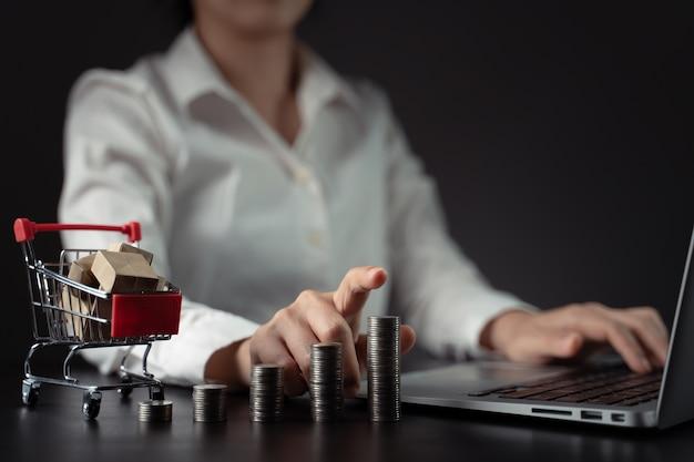 Bliska strzał kobiety wpisując na laptopie z mini koszyk i stos monet. koncepcja marketingu finansowego.