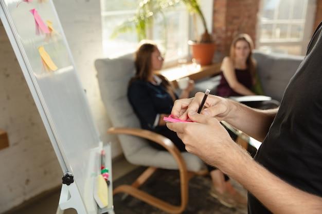 Bliska strzał męskich rąk podczas kreatywnego spotkania i burzy mózgów. mężczyźni i kobiety spotykają się w biurze, aby zaplanować swoją przyszłą pracę. pomysł na biznes.