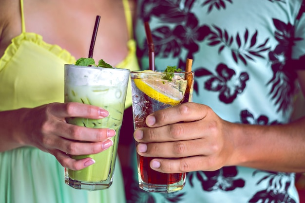 Bliska strzał młoda uśmiechnięta para cieszy się ich drinkami, okrzyki do aparatu, matcha latte i lemoniady jagodowej, koktajle na imprezie, stonowane jasne kolory.