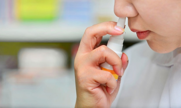 Bliska strzał młodej kobiety przy użyciu leku w sprayu do nosa w aptece