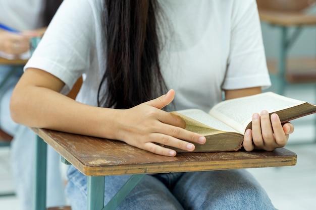 Bliska strzał młodych studentek otwiera i czyta książkę w klasie z tłem kolegów. studenci studiujący w klasie uniwersyteckiej. edukacja pień fotografia.