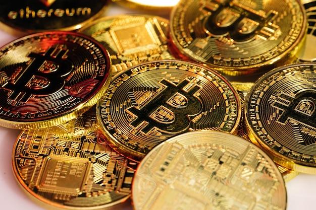 Bliska strzał monet bitcoins na białym tle na tle płyty głównej. kryptowaluta, bitcoin. btc, bit coin. technologia blockchain, wydobywanie bitcoinów.