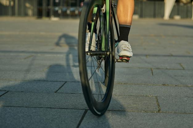 Bliska strzał nogi kobiety rowerzystki w butach rowerowych, jazda na rowerze w mieście