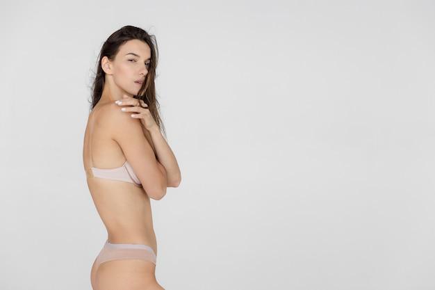 Bliska strzał pasuje kobieta w bieliźnie na białym tle tułowia szczupła atrakcyjna kobieta z płaskim brzuchem w białej bieliźnie kopiuje miejsce na tekst wysokiej jakości zdjęcie