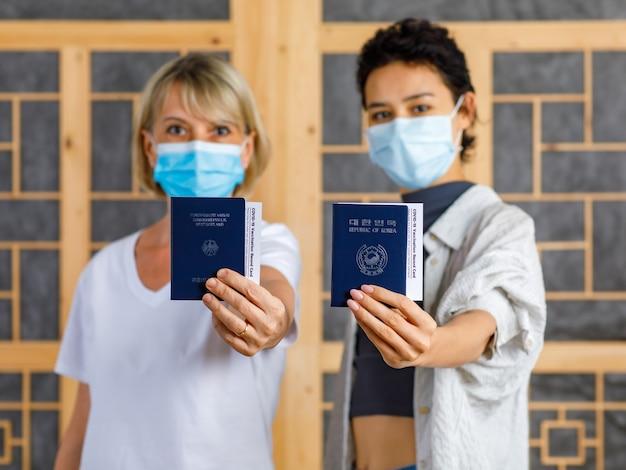 Bliska strzał paszportu deutschland i republiki korei z certyfikatem karty szczepień przeciwko covid-19 w kaukaskich blond i azjatyckich rękach kobiet, które noszą maskę w rozmytym tle.