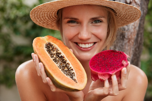 Bliska strzał piękna uśmiechnięta kobieta o atrakcyjnym wyglądzie, przyjemnym uśmiechu, trzyma papaję i smoczy owoc, pozuje na świeżym powietrzu w tropikalnym miejscu, zjada soczyste pyszne owoce. letnia wycieczka.
