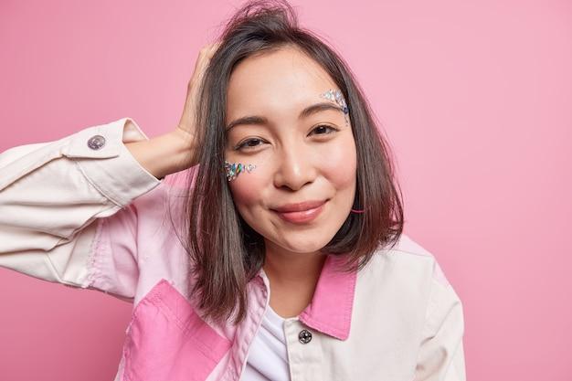 Bliska strzał pięknej azjatyckiej tysiącletniej dziewczyny z ciemnymi włosami naturalny makijaż zdrowej skóry ma błyszczące kamienie na twarzy ubranej w modną kurtkę na białym tle nad różową ścianą patrzy zadowolony