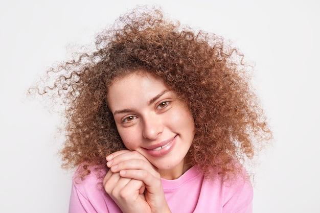 Bliska strzał pięknej młodej modelki trzyma ręce w pobliżu twarzy przechyla głowę ma naturalne kręcone włosy zdrową skórę podziwia coś pięknego na białym tle nad białą ścianą. wyrazy ludzkiej twarzy