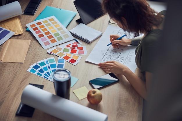 Bliska strzał procesu pracy projektanta wnętrz robienia notatek na planie wybierając kolor