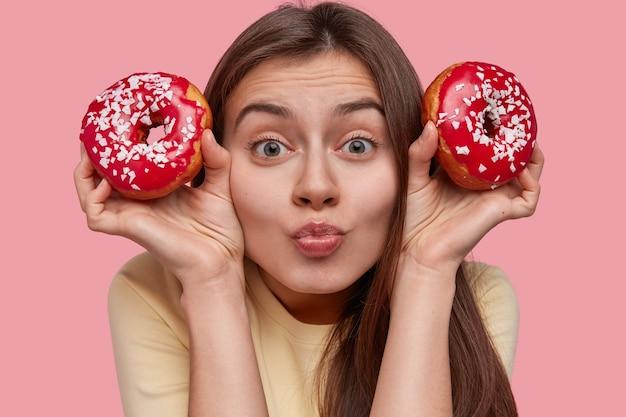 Bliska strzał przyjemnie wyglądającej brunetki młodej kobiety ciekawie patrzy w kamerę, ma minimalny makijaż, zielone oczy, wydymane wargi
