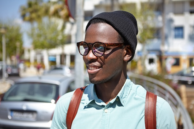 Bliska strzał przystojnego czarnego europejskiego hipstera z plecakiem spacerującym po metropolii, eksplorującego lokalizacje podczas podróży po europie, stojącego w otoczeniu miejskim, noszącego okulary przeciwsłoneczne i kapelusz