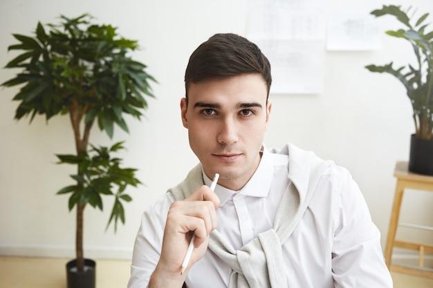 Bliska strzał przystojny, gładko ogolony, młody pracownik brunetka ubrany w stylowe ubranie o zamyślonym wyglądzie, trzymając ołówek, siedzący we wnętrzu biura