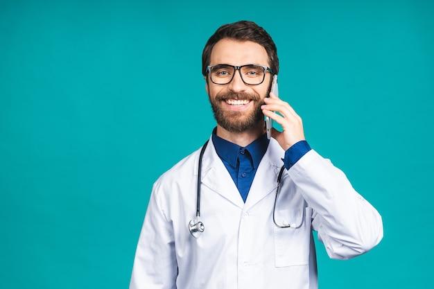 Bliska strzał przystojny młody lekarz mężczyzna na białym tle na niebieskim tle rozmawia na smartfonie, uśmiechając się pozytywnie. korzystanie z telefonu komórkowego.