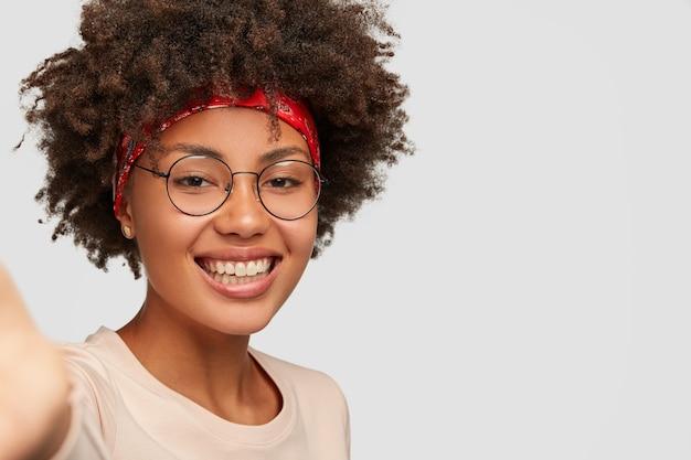 Bliska strzał radosna kobieca dziewczyna ma zębaty uśmiech, fryzurę afro, piękną, czystą skórę, nosi przezroczyste okulary, rozciąga rękę, trzymając nierozpoznawalne urządzenie, robi selfie na białej ścianie